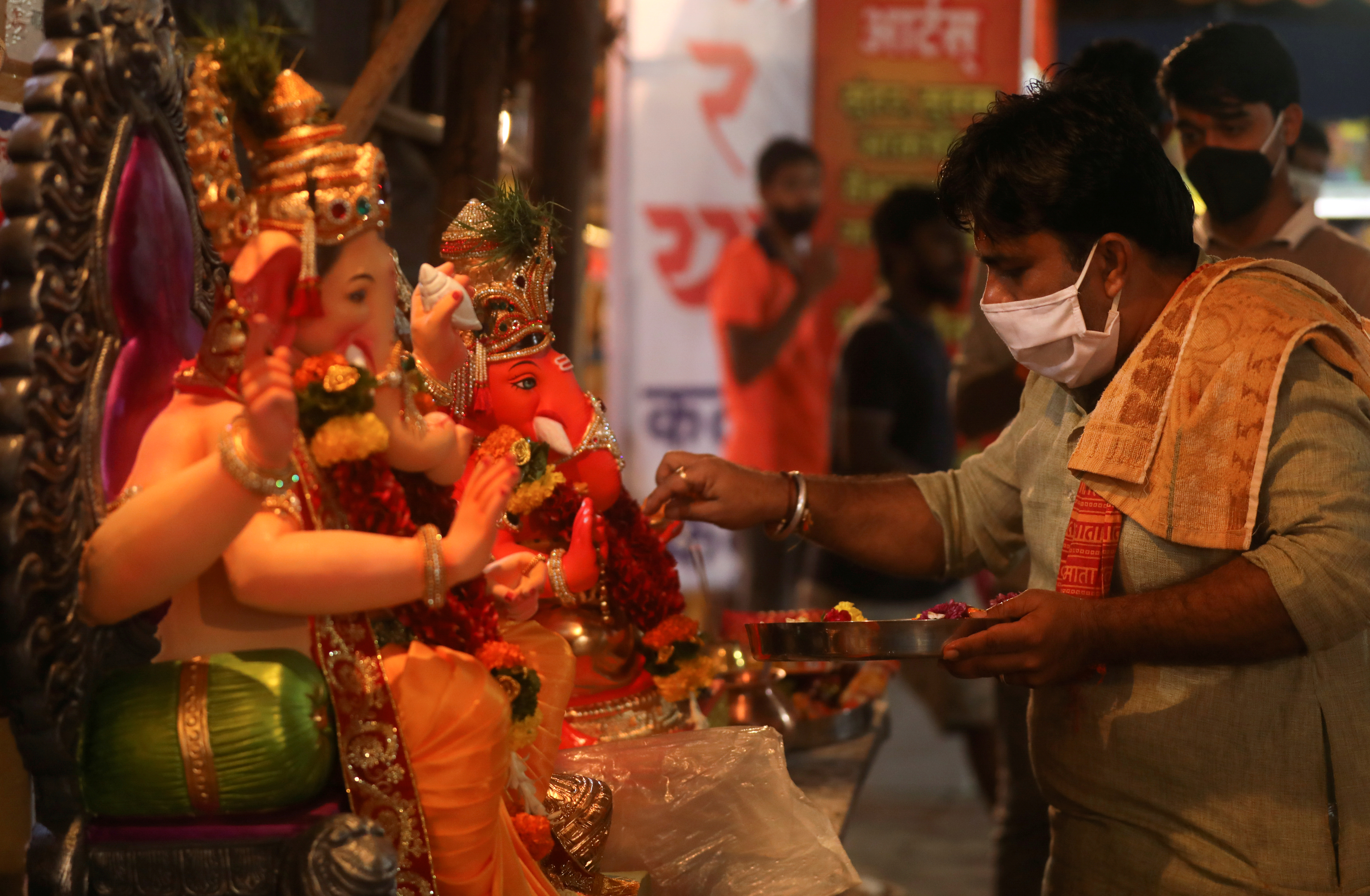 A Hindu priest wearing a protective face mask conducts a puja in front of idols of Hindu God Ganesh,  the deity of prosperity, before they can be taken home ahead of the Ganesh Chaturthi festival in Mumbai, India August 21, 2020. Photo: Reuters