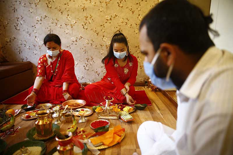 Women along with a priest perform prayer rituals at their home during Teej festival in Lalitpur, on Friday, August 21, 2020. The government has issued a week-long prohibitory order in the valley and restricted public gatherings to prevent the spread of novel coronavirus.  Devotees and revellers are confined to their homes as the festival coincides with the second day of the prohibitory order. Photo: Skanda Gautam/THT