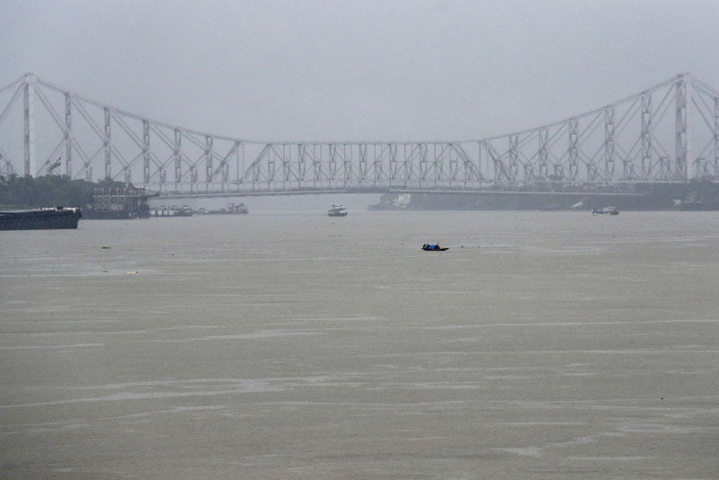 A country fishing moves on the Hooghly River as the city landmark Howrah Bridge is seen behind during a rainy day in Kolkata, India, Thursday, Aug. 6, 2020. Photo: AP