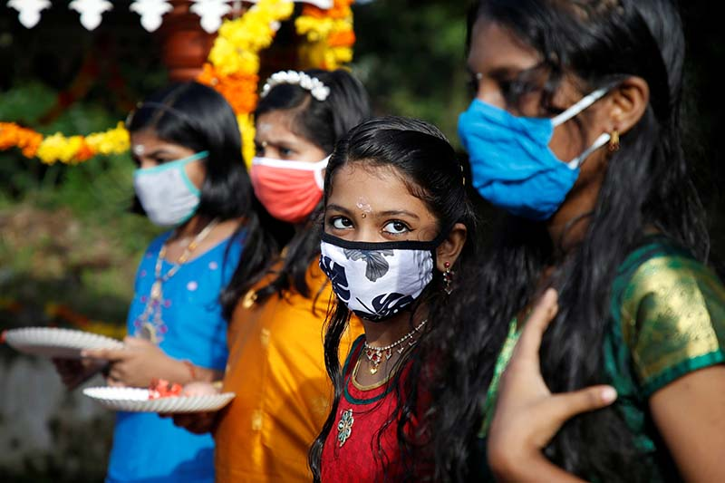 Girls wearing protective face masks wait to pray inside temple premises on the occasion of the annual harvest festival of Onam, amidst the spread of the coronavirus disease (COVID-19), on the outskirts of Kochi, India, on August 31, 2020. Photo: Reuters