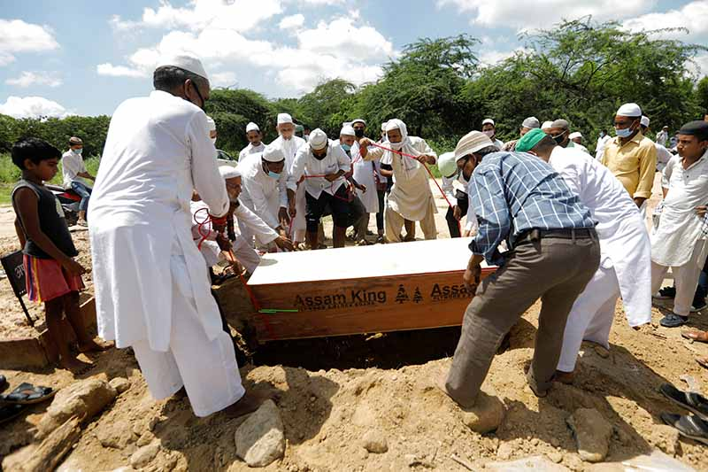 Relatives lower a coffin with the body of a woman who died from the coronavirus disease (COVID-19), during her funeral at a graveyard in New Delhi, India, on Saturday, August 22, 2020. Photo: Reuters