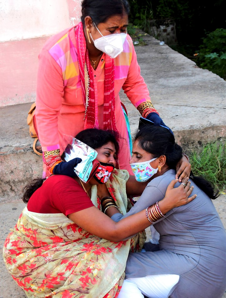Relatives of victims of a crane collapse mourn outside King George Hospital in Vishakhapatnam, a port city in Andhra Pradesh state, India, Saturday, Aug. 1, 2020. A huge crane collapsed during load testing at a government-run shipyard in southern India on Saturday, killing at least 11 workers, a district administrator said. (AP Photo)