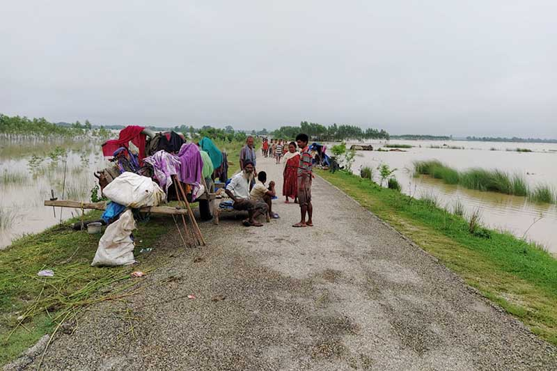 Families displaced by floods are seen sheltering at the Postal Highway, in Bhajani Municipality of Kailali district, on Saturday, August 1, 2020. Photo: Tekendra Deuba/THT