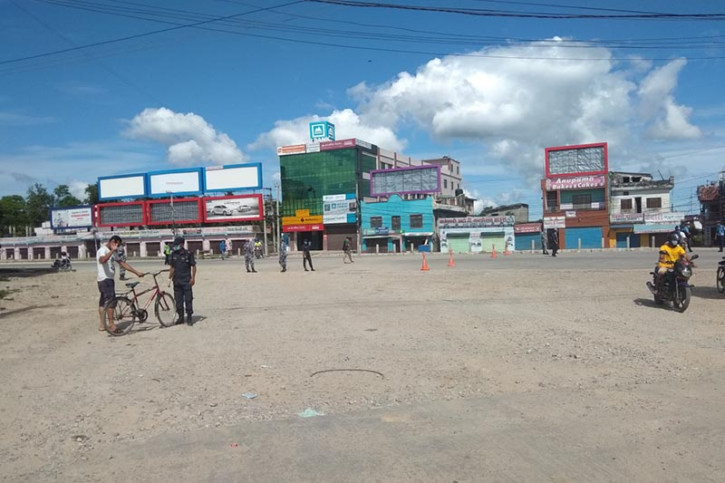 This image shows a security personnel inquiring a cyclist while a motorcyclist is passing by in Dhangadhi Sub-metropolitan City, Kailali district, on Friday, August 21, 2020. Photo: Tekendra Deuba/THT