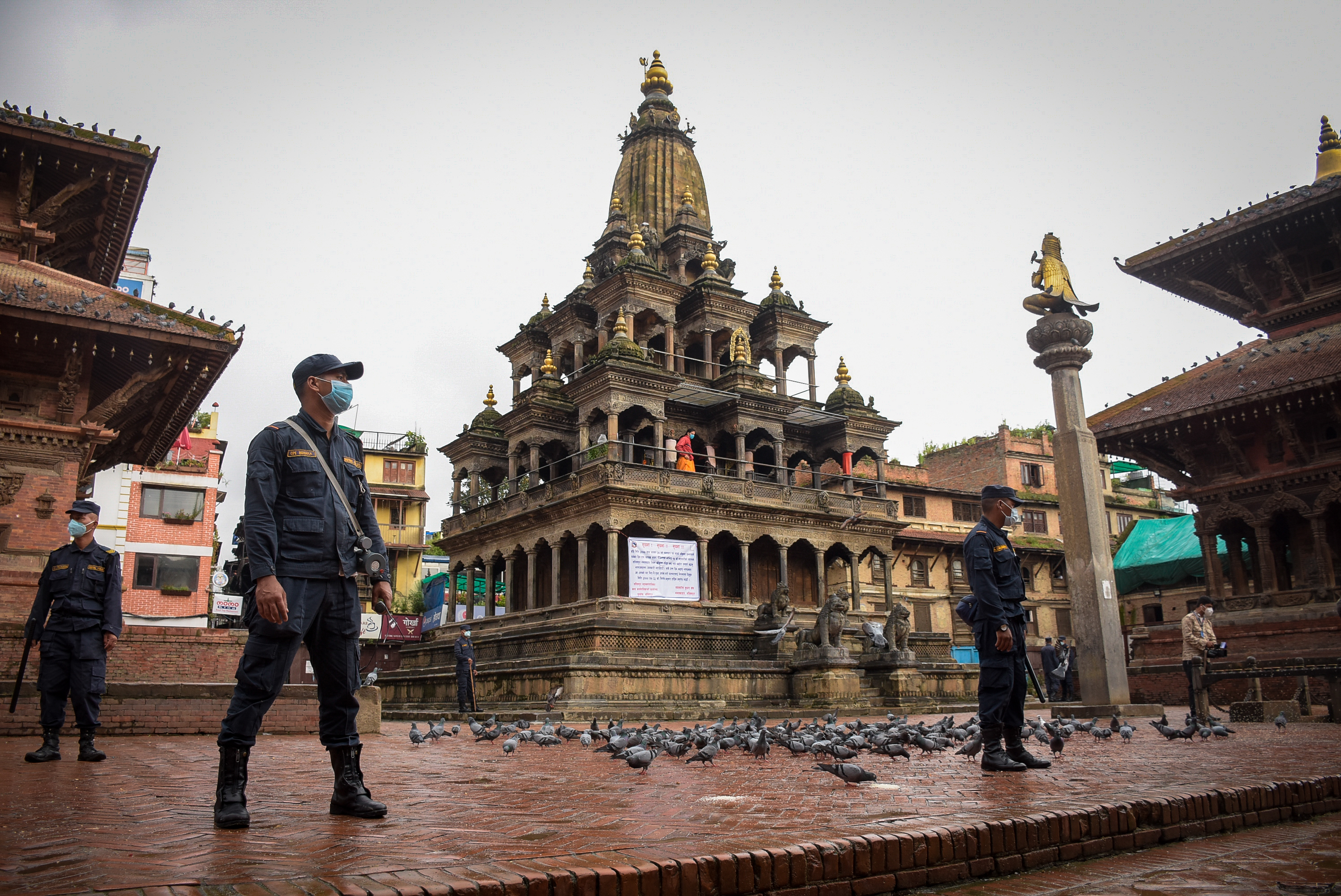 Security personnel stand guard at the  premises of Krishna Mandir, during  Krishna Janmashtami, at Patan Durbar Square, in Lalitpur, Tuesday, August 11, 2020. Due to the ongoing coronavirus pandemic this year, entry inside the temple has been restricted. Photo: Naresh Shrestha/THT