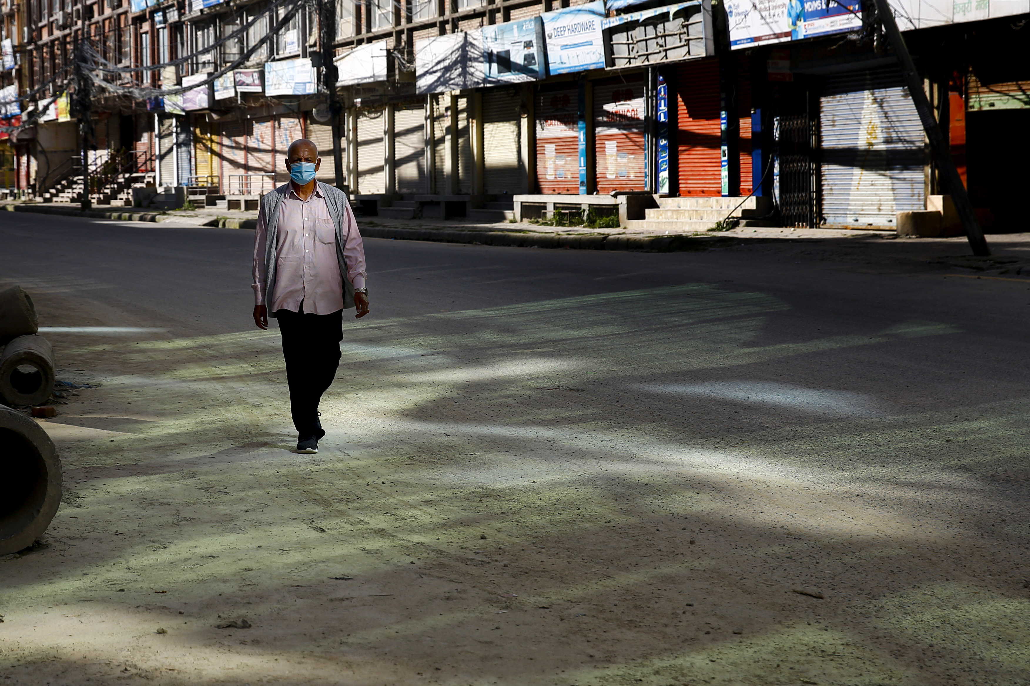 A man walks along the deserted road on the third day of the week-long government imposed lockdown, amid concerns over the rise in coronavirus disease, in Kathmandu, on Saturday, August 22, 2020. Photo: Skanda Gautam/THT