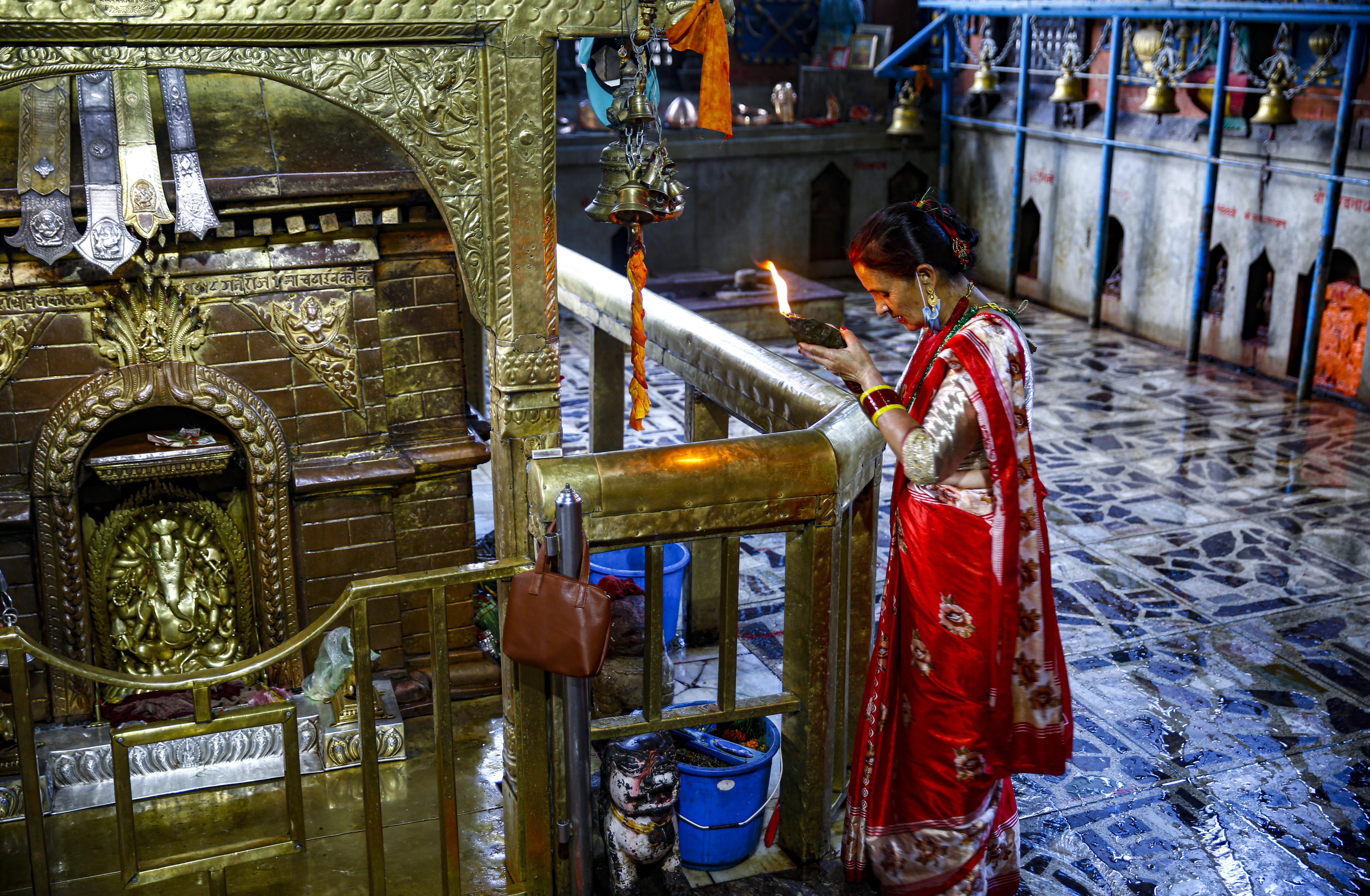 A woman prays during the Ganesh Chaturthi festival, at a deserted Ganesh Temple, on the third day of week-long government imposed lockdown, amid concerns over the rise of coronavirus disease in Kathmandu, on Saturday, August 22, 2020. Photo: Skanda Gautam/THT