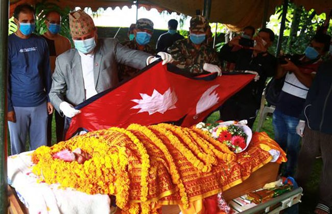 Deputy Prime Minister and Minister of Defence Ishwar Pokhrel draping the national flag over the body of National Poet Madhav Prasad Ghimire at his residence in Lainchaur, Kathmandu, on Wednesday, August 19, 2020. Photo: RSS