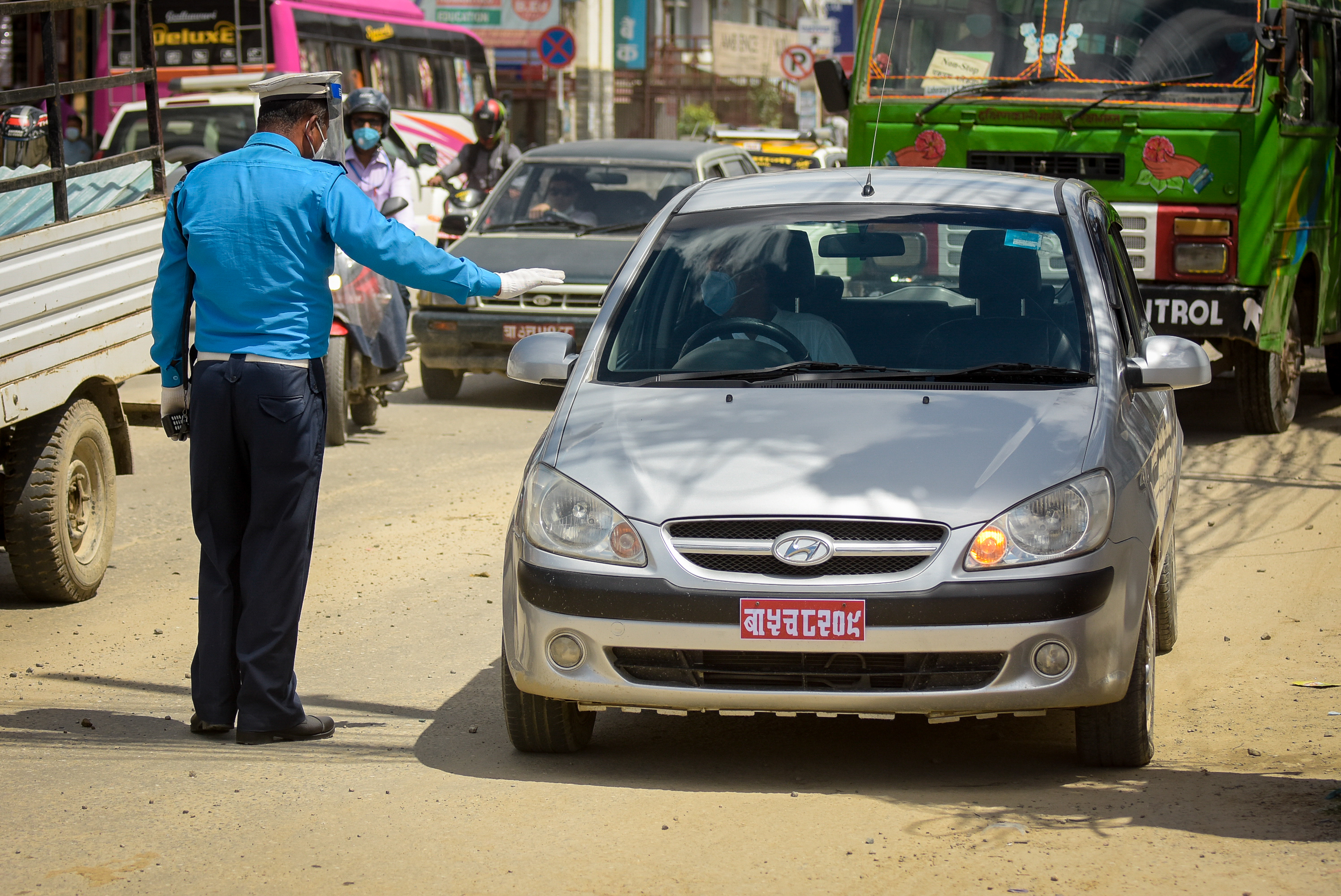 Traffic police personnel stop vehicles for violating the odd-even rule re-imposed by the Ministry of Home Affairs, to reduce traffic movement on the city roads, to curb the COVID-19 transmission, at Satdobato, in Lalitpur, on Thursday, August 6, 2020. Photo: Naresh Shrestha/THT