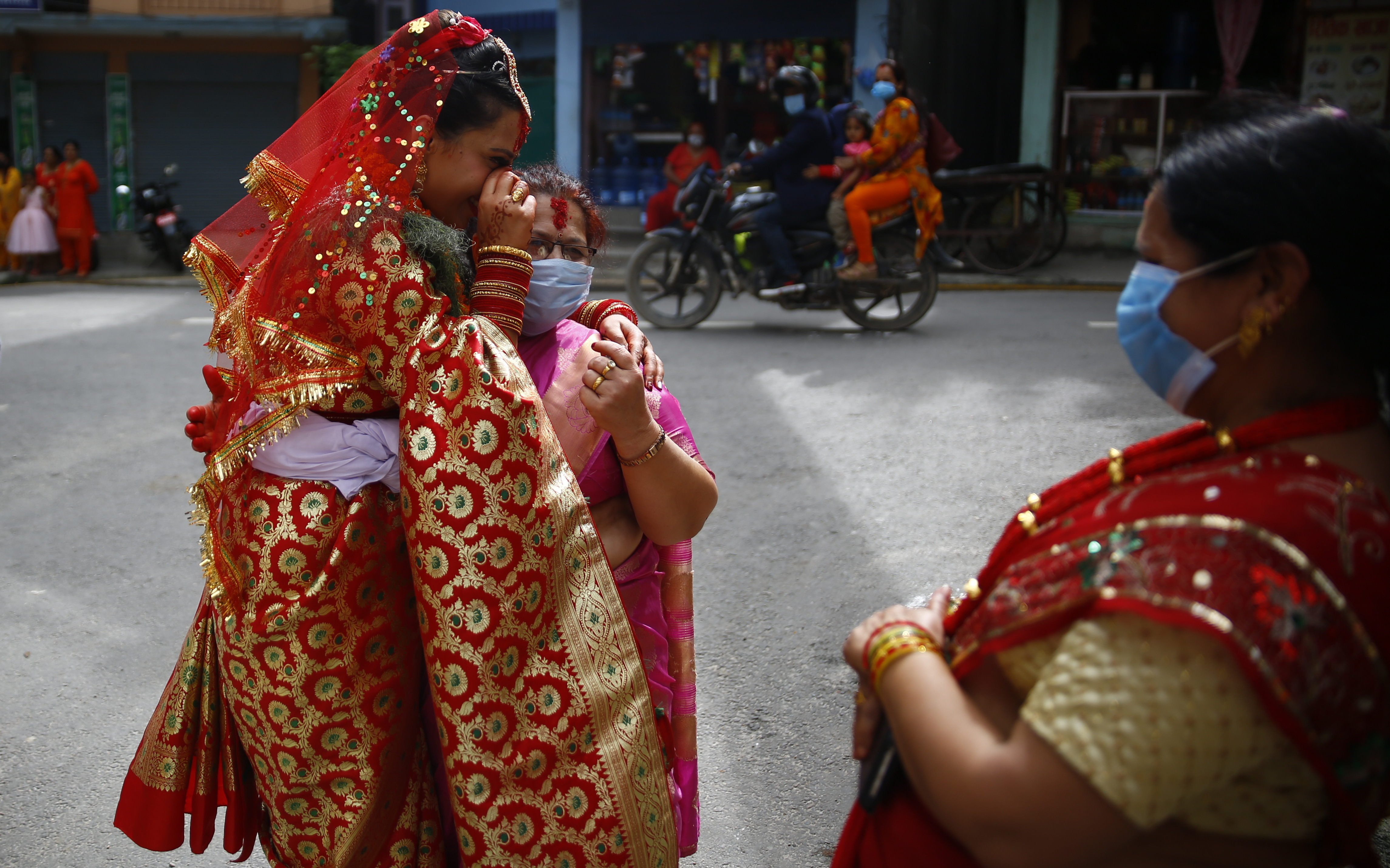A bride embraces her mother after the wedding ceremony, outside their house, at a time when the government has restricted public gatherings as a precaution against further transmission of COVID-19, in Kathmandu, on Tuesday, August 11, 2020. Photo: Skanda Gautam/THT