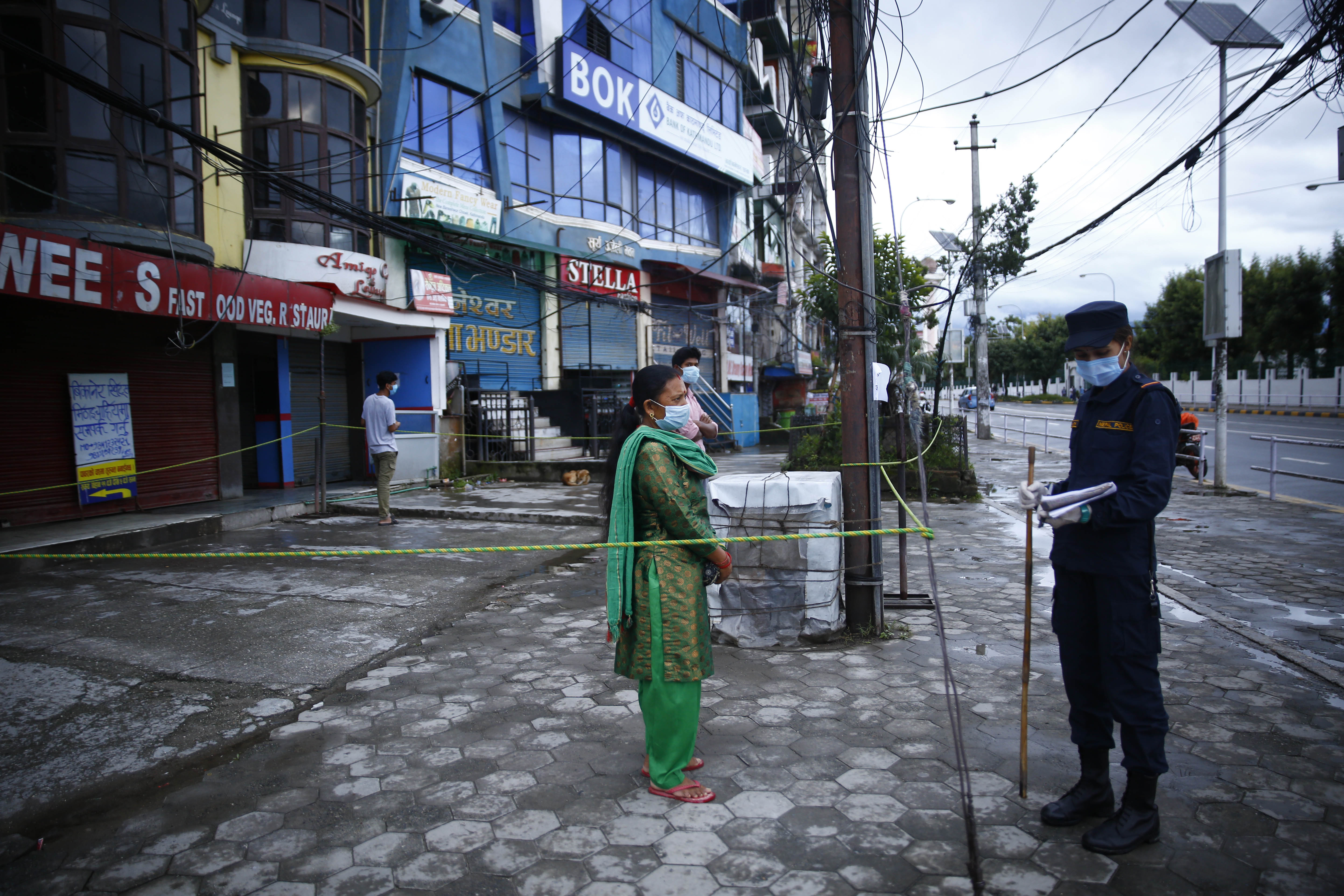 Police personnel questioning a woman for defying prohibitory order in Kathmandu, on Thursday, August 20, 2020. Photo: Skanda Gautam/THT