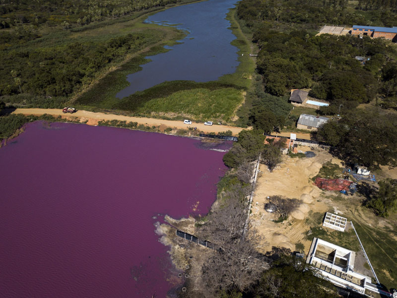 A road divides the Cerro Lagoon, where the water below the road is colored and the Waltrading S.A. tannery stands on the bank, bottom right, in Limpio, Paraguay, Wednesday, Aug. 5, 2020. Photo: AP