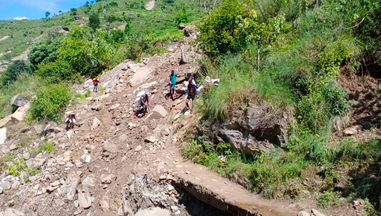People are seen traversing the road swept away by landslide in Amkot of Budhiganga Municipality-1 of Bajura along the Sanfe-Martadi road section. Photo: Prakash Singh/ THT