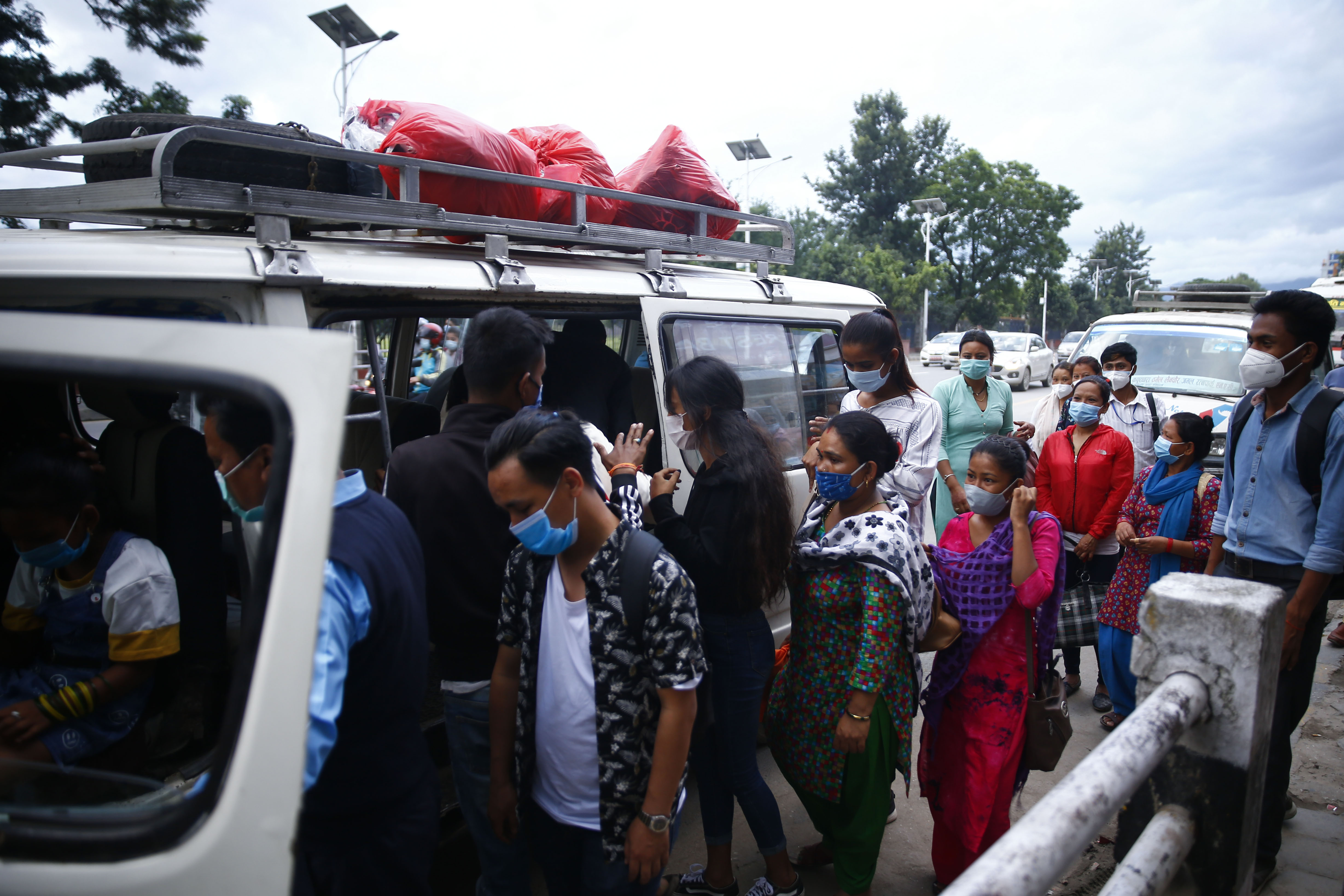 People queue to get into a public vehicle without maintaining a safe physical distance, amid surging coronavirus cases, in Kathmandu, on Thursday, August 06, 2020. Photo: Skanda Gautam/THT