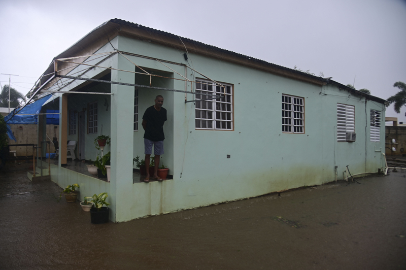 A resident stands on the porch of his home flooded by rains caused by Tropical Storm Laura in Salinas, Puerto Rico, Saturday, Aug. 22, 2020. Laura began flinging rain across Puerto Rico and the Virgin Islands on Saturday morning and was expected to drench the Dominican Republic, Haiti and parts of Cuba during the day on its westward course. Photo: AP