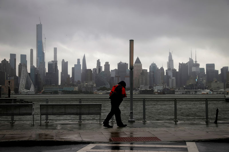 A man walks into heavy wind and rain along the waterfront of the Hudson River in front of the New York City skyline during Tropical Storm Isaias in Weehawken, New Jersey, U.S., August 4, 2020. Photo: Reuters