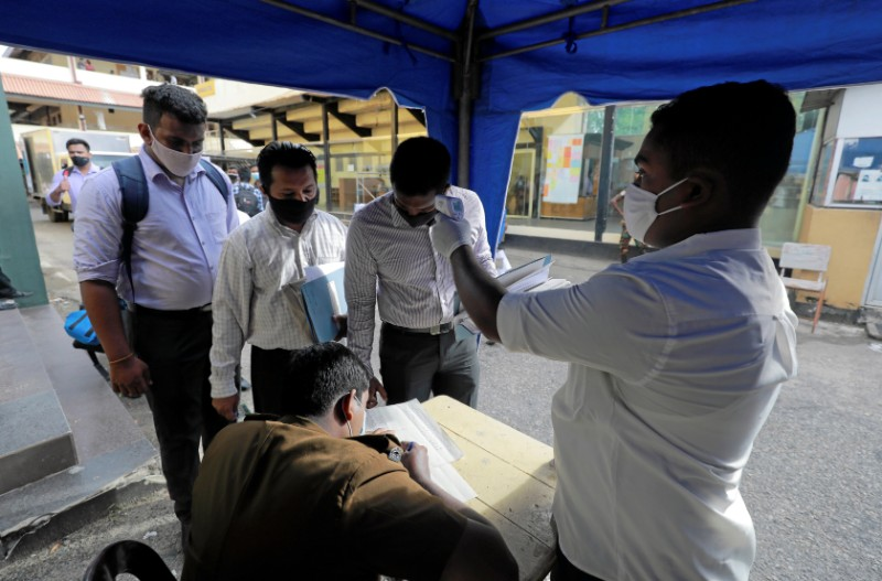 A health official takes the temperature of election officials wearing protective masks at a ballot boxes and papers distribution center ahead of country's parliamentary election which scheduled for August 5th, in Colombo, Sri Lanka, August 4, 2020. Photo: Reuters
