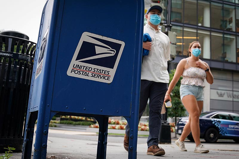 People wear protective masks as they walk past a US Postal Service blue collection box on Capitol Hill in Washington, US, on August 13, 2020. Photo: Reuters