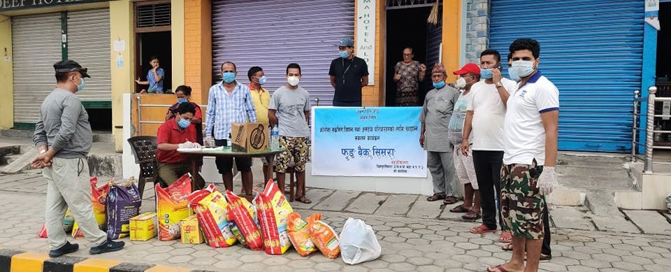 People gathering around a stock of food items to be distributed among needy people, in Bara, on Saturday. Photo: THT