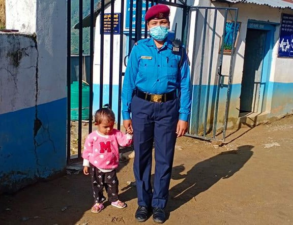A female constable on duty with her daughter at Bajura District Police Office, on Sunday. Photo: THT
