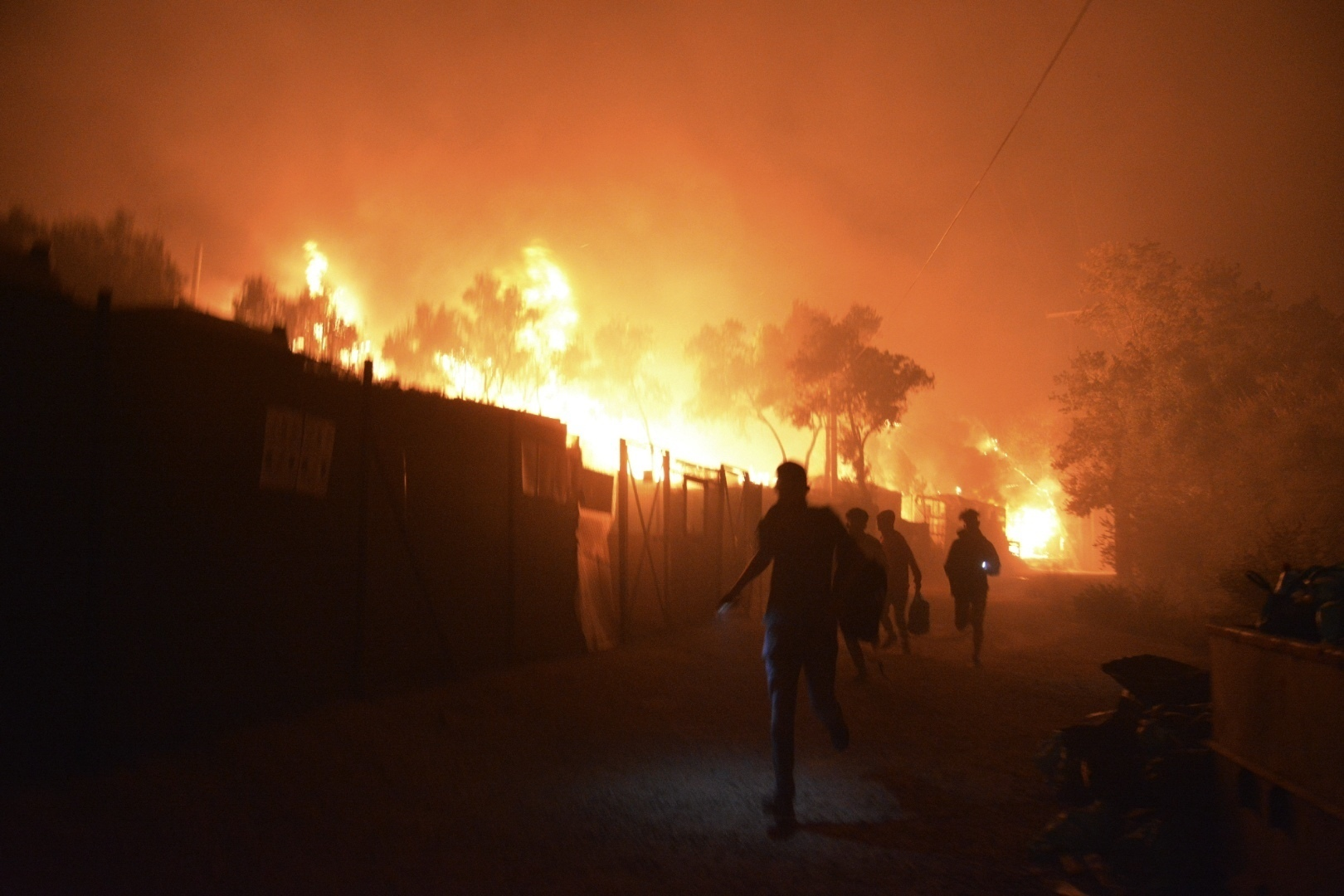 Refugees and migrants run as fire burns in the Moria refugee camp on the northeastern Aegean island of Lesbos, Greece, on Wednesday, Sept. 9, 2020. Fire Service officials say a large refugee camp on the Greek island of Lesbos has been partially evacuated despite a COVID-19 lockdown after fires broke out at multiple points around the site early Wednesday. Photo: AP