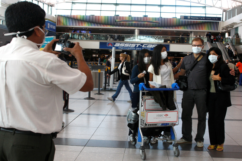 File - Passengers wearing protective masks pose for a photograph before boarding at the international airport in Buenos Aires April 30, 2009. Photo: Reuters