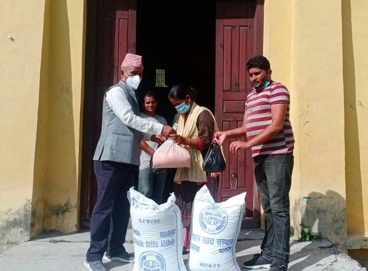 Provincial Assembly member Baldev Regmi handing over food items to a local woman in Budhinanda Municipality, Bajura, on Sunday. Photo: THT
