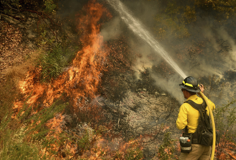 A firefighter puts out a hot spot along Highway 38 northwest of Forrest Falls, Calif., as the El Dorado Fire continues to burn Thursday afternoon, Sept. 10, 2020. Photo: Will Lester/The Orange County Register/SCNG via AP