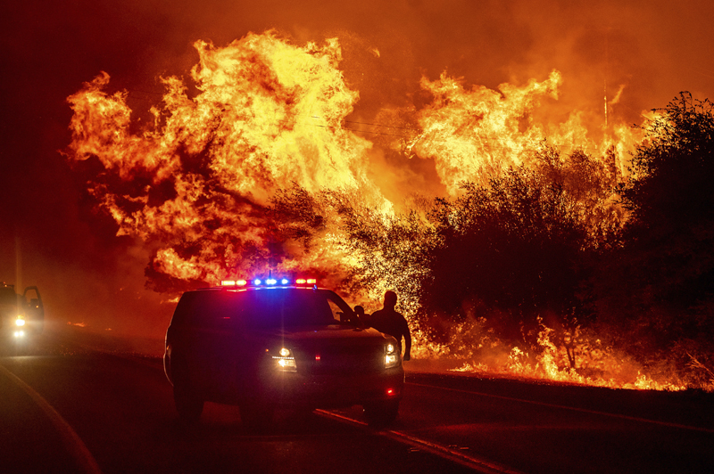 Flames lick above vehicles on Highway 162 as the Bear Fire burns in Oroville, Calif., on Wednesday, Sept. 9, 2020. Photo: AP