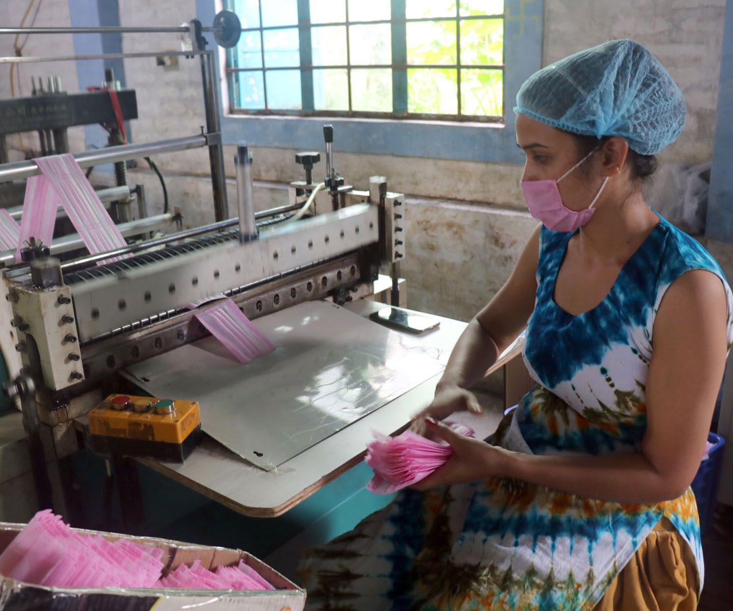 A worker tending to a machine producing face masks in Kshetrapur, Chitwan, on Wednesday. Photo: RSS