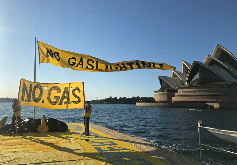 Ambrose Hayes, a 15-year-old climate change activist, displays a banner as he rides on a barge during an event as part of the Fund Our Future Not Gas climate rally in Sydney Harbour, Sydney, Australia, September 25, 2020.  Photo:  Reuters