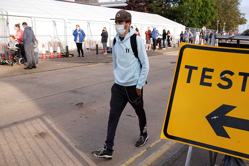A man walks past people queueing outside a test centre, following an outbreak of the coronavirus disease (COVID-19), in Southend-on-sea, Britain, on September 17, 2020. Photo: Reuters