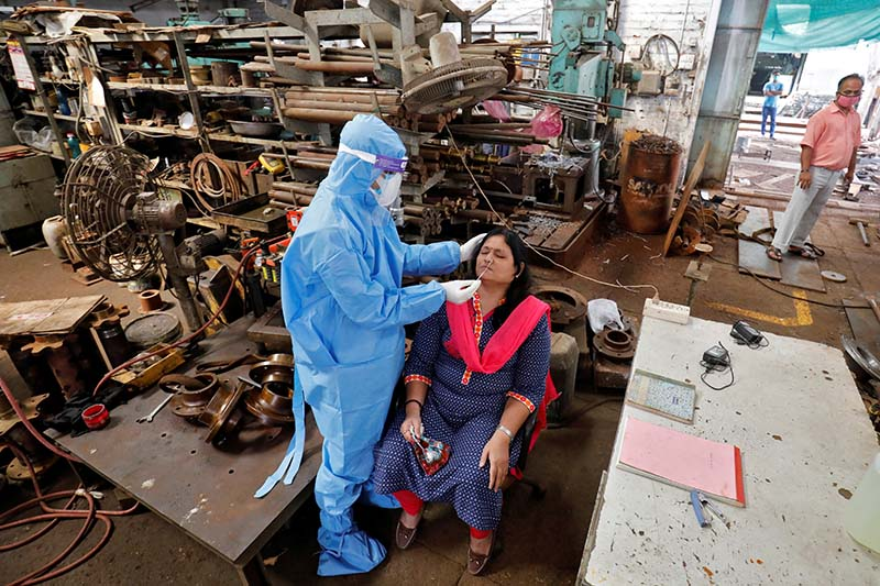 A healthcare worker wearing personal protective equipment (PPE) takes swab from an employee for a rapid antigen test inside a factory, amidst the coronavirus disease (COVID-19) outbreak, in Ahmedabad, India, on Friday, September 11, 2020. Photo: Reuters