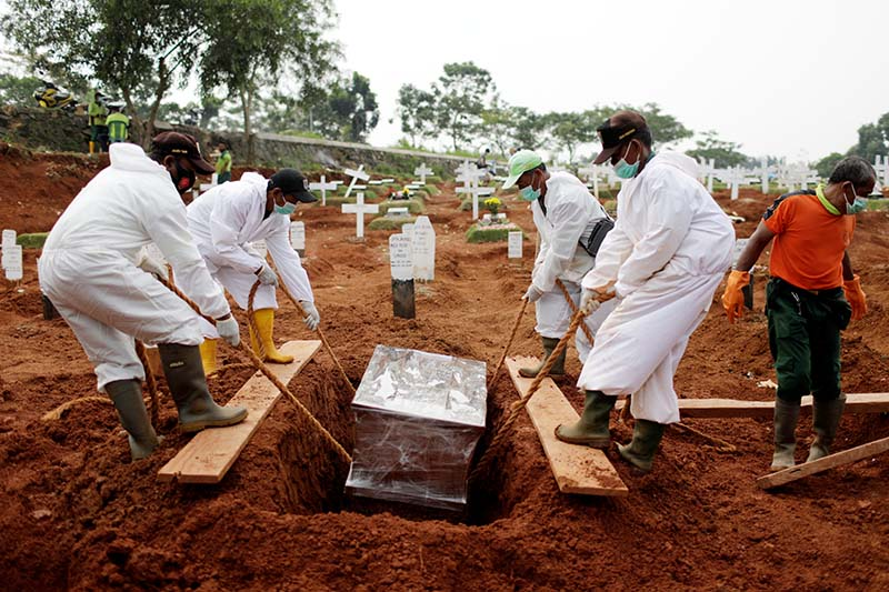 Workers wearing protective suits bury a coffin at the burial area provided by the government for victims of the coronavirus disease (COVID-19) at Pondok Ranggon cemetery complex, as the outbreak continues in Jakarta, Indonesia, on September 24, 2020. Photo: Reuters