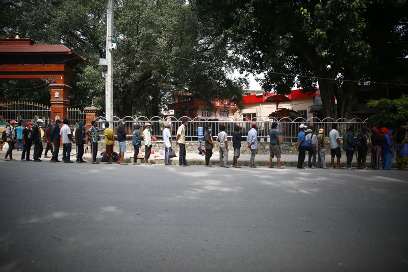 Daily wagers and homeless people queue for free hot meals during the lockdown at Mahalaxmisthan in Lalitpur, on Saturday, September 5, 2020. Photo: Skanda Gautam/THT