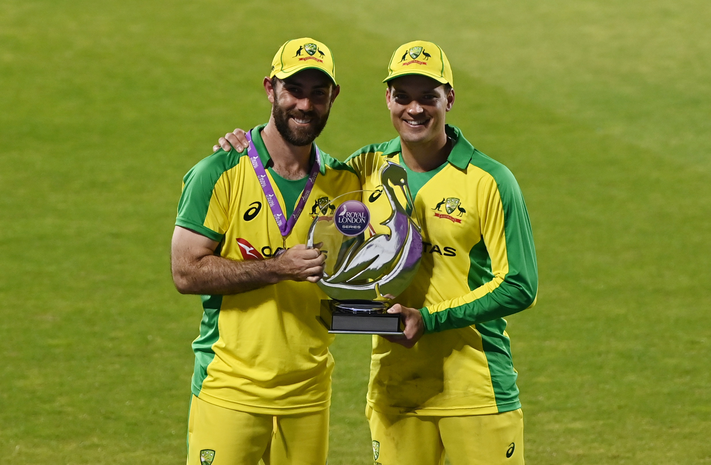 Australia's Glenn Maxwell and Alex Carey pose with the trophy after winning the match and the series. Photo: Reuters
