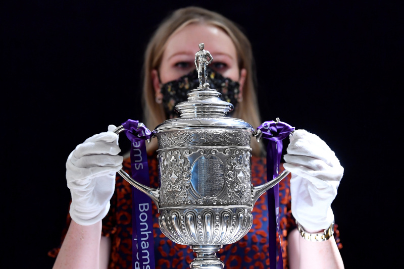 Laurel Kemp, Cataloguer at Bonhams, holds the FA Cup 1896-1910 ahead of a forthcoming auction of Spectacular Sporting Trophies and Memorabilia, in London, Britain, September 7, 2020.  Photo: Reuters