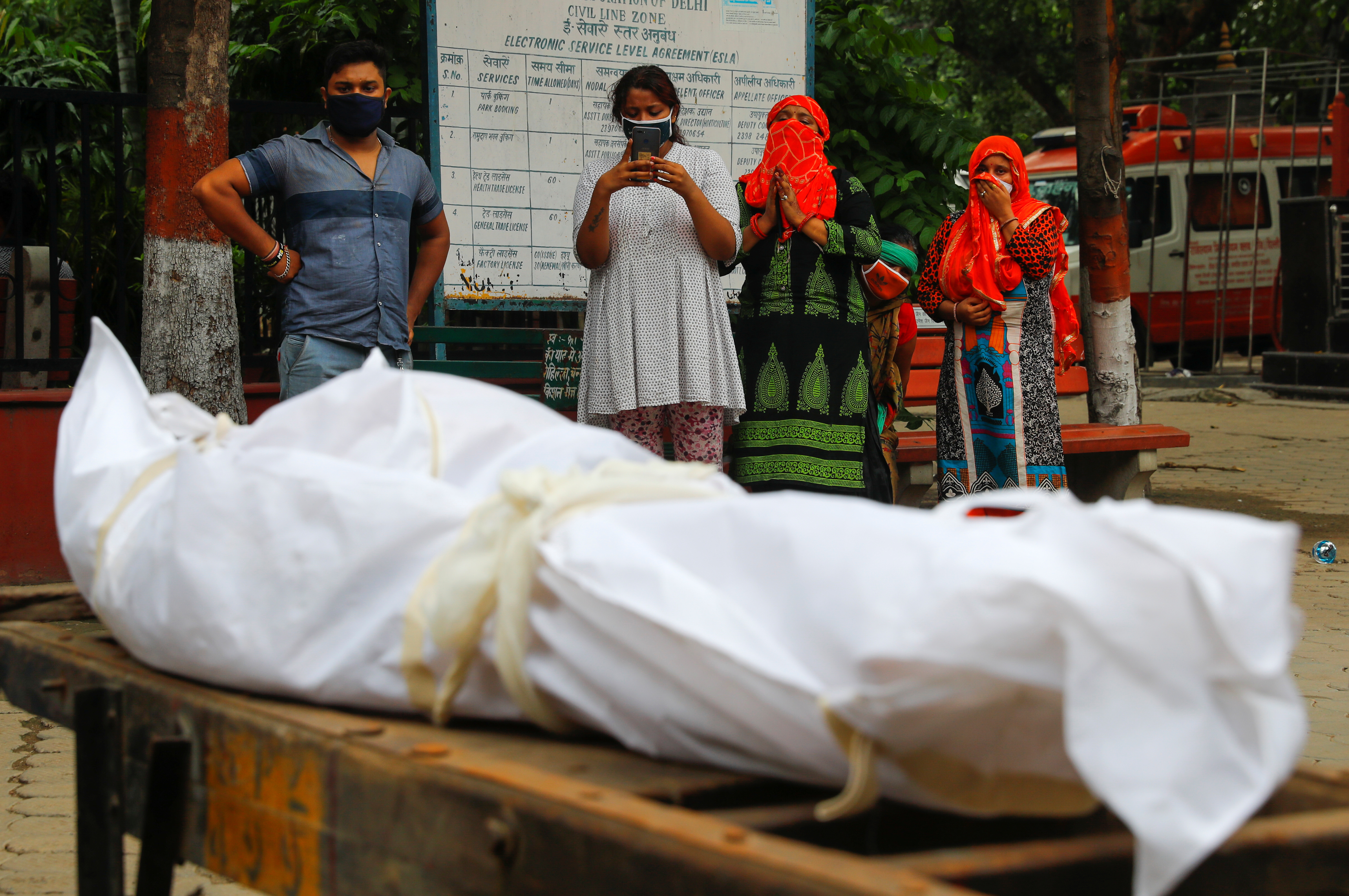 Relatives mourn as they stand next to the body of a man who died due to the coronavirus disease (COVID-19), at a crematorium, in New Delhi, India September 7, 2020. Photo: Reuters