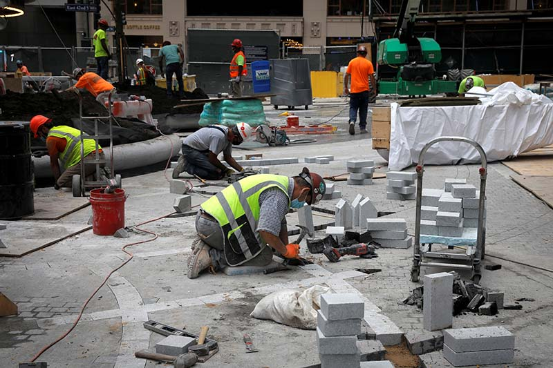 Workers finish the entry plaza outside the 77 story One Vanderbilt office tower, the latest super-tall skyscraper to grace New York's iconic skyline, is set to open while the coronavirus disease (COVID-19) keeps the largest and richest US office market almost empty, in midtown Manhattan, New York City, New York, US, September 9, 2020. Photo: Reuters