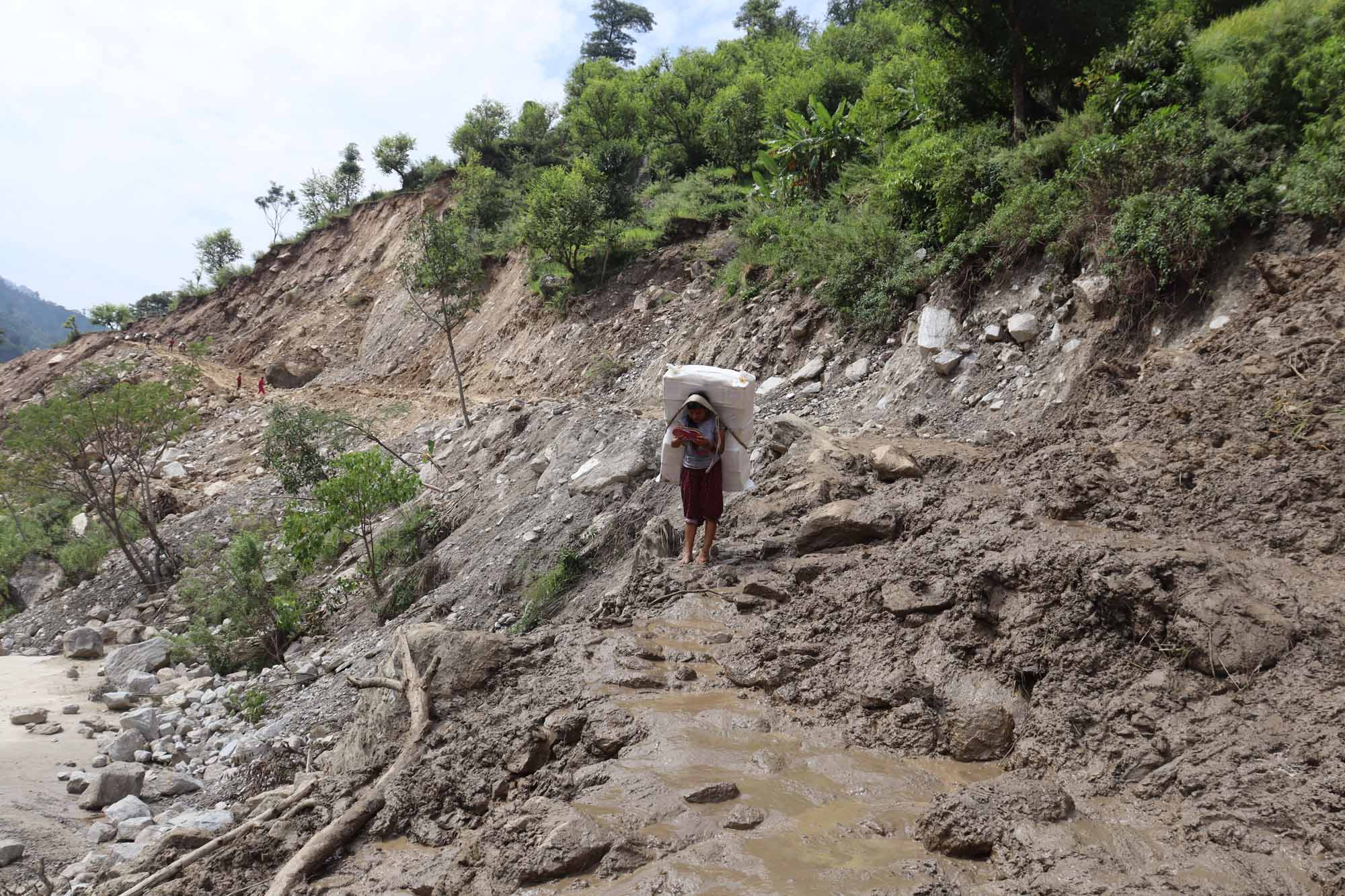 A girl carrying goods is seen walking along the Sanphe-Martadi road section damaged by a landslide in Amkot of Budhiganga Municipality in Bajura on Monday, September 28, 2020. Photo: Prakash Singh/THT