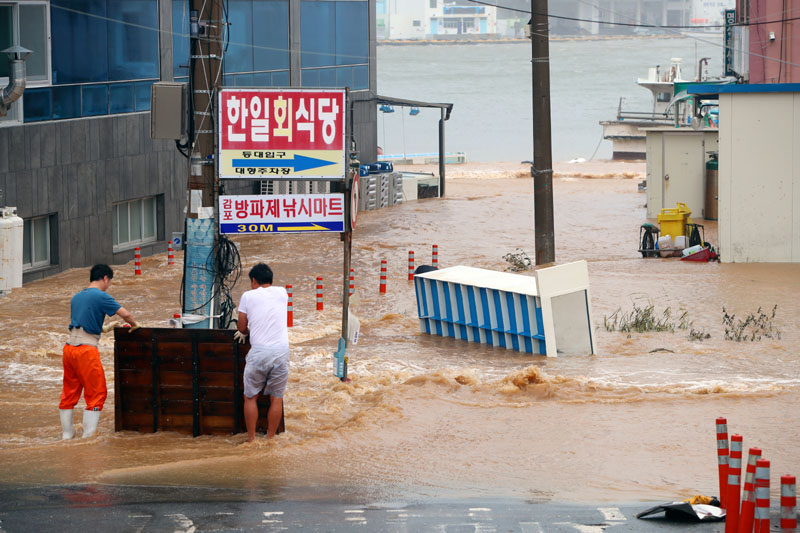 Men stand on a street submerged by typhoon Haishen in Gyeongju, South Korea, September 7, 2020.   Photo:  Yonhap via Reuters