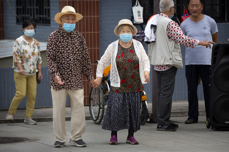 An elderly couple wearing face masks to protect against the coronavirus walks at a public park in Beijing, Saturday, Sept. 12, 2020. Photo: AP