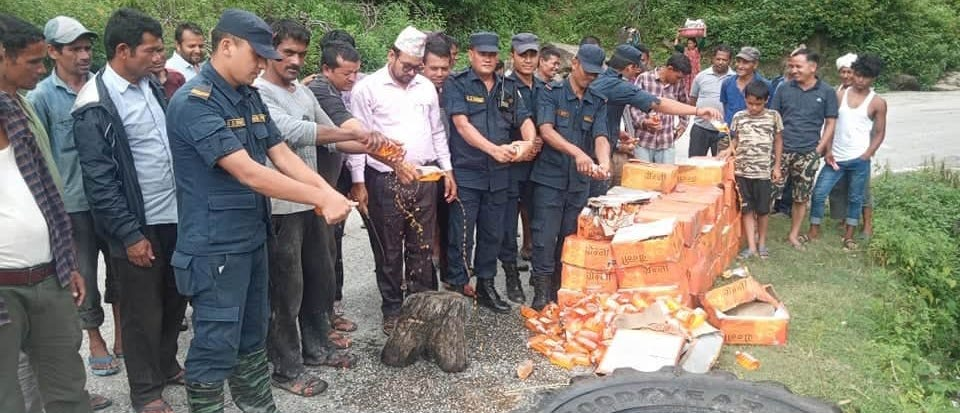 Police destroying the seized liquor in Budhiganga Municipality, Bajura, on Tuesday. Photo: THT