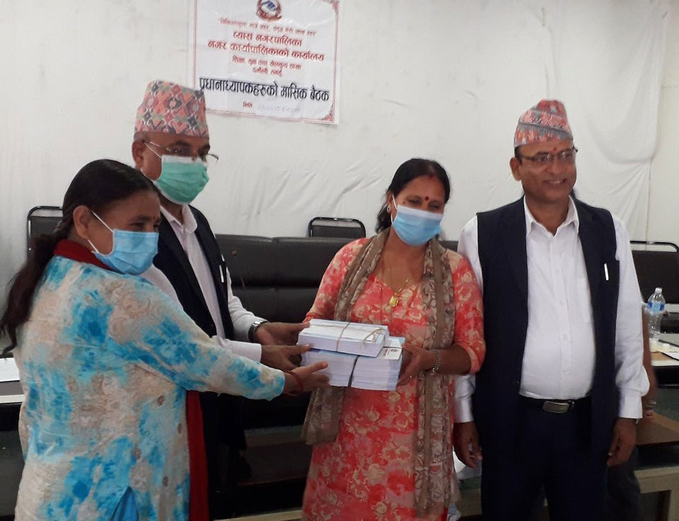 Byas Municipality Mayor Baikuntha Neupane handing over logbooks and teachersu2019 diaries to head teachers in Byas Municipality Office, Tanahun, on Tuesday. Photo: THT