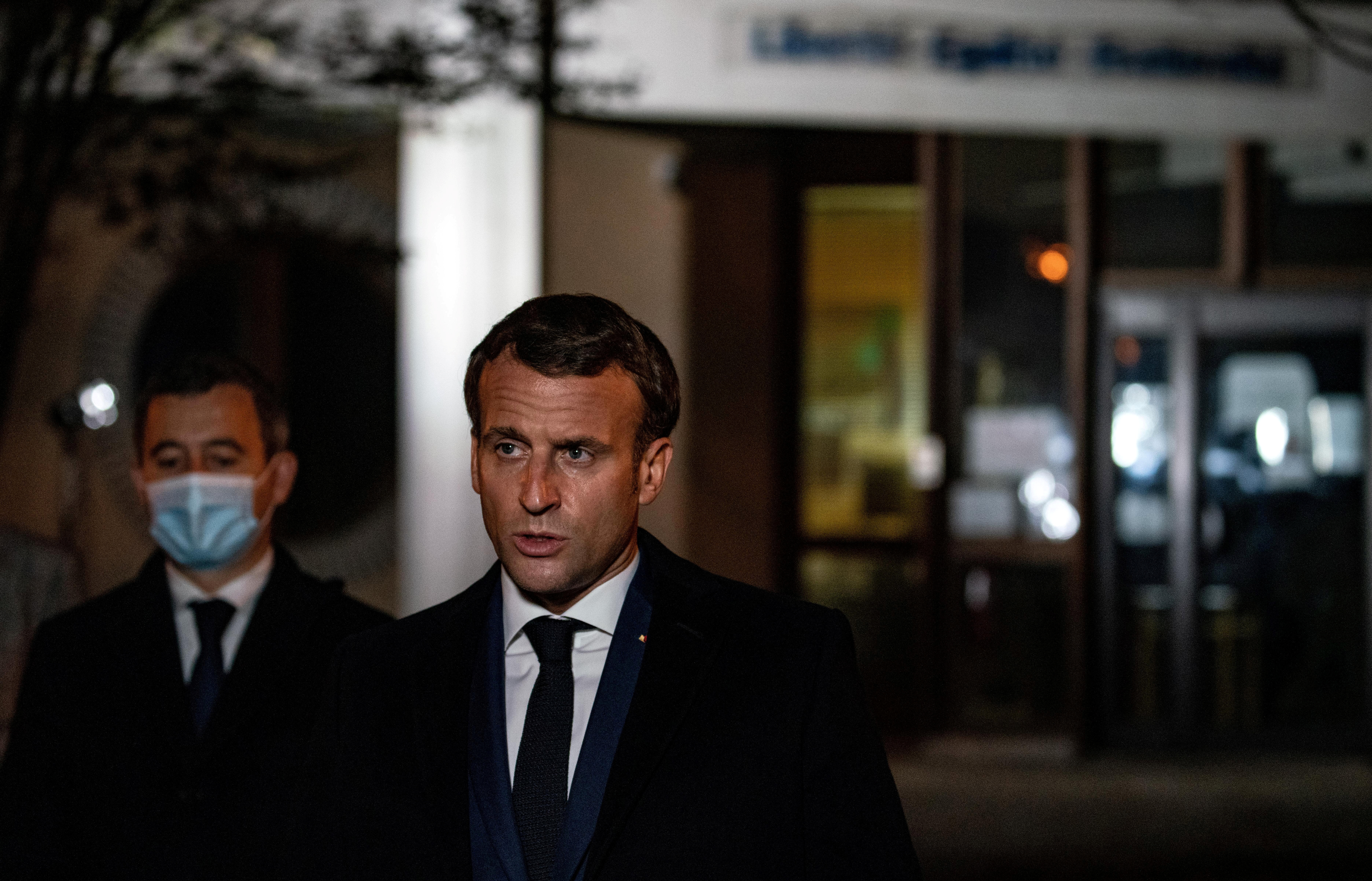French President Emmanuel Macron flanked by French Interior Minister Gerald Darmanin speaks following a stabbing attack in the Conflans-Sainte-Honorine suburb of Paris, France, October 16, 2020. Abdulmonam Eassa/Pool via REUTERS
