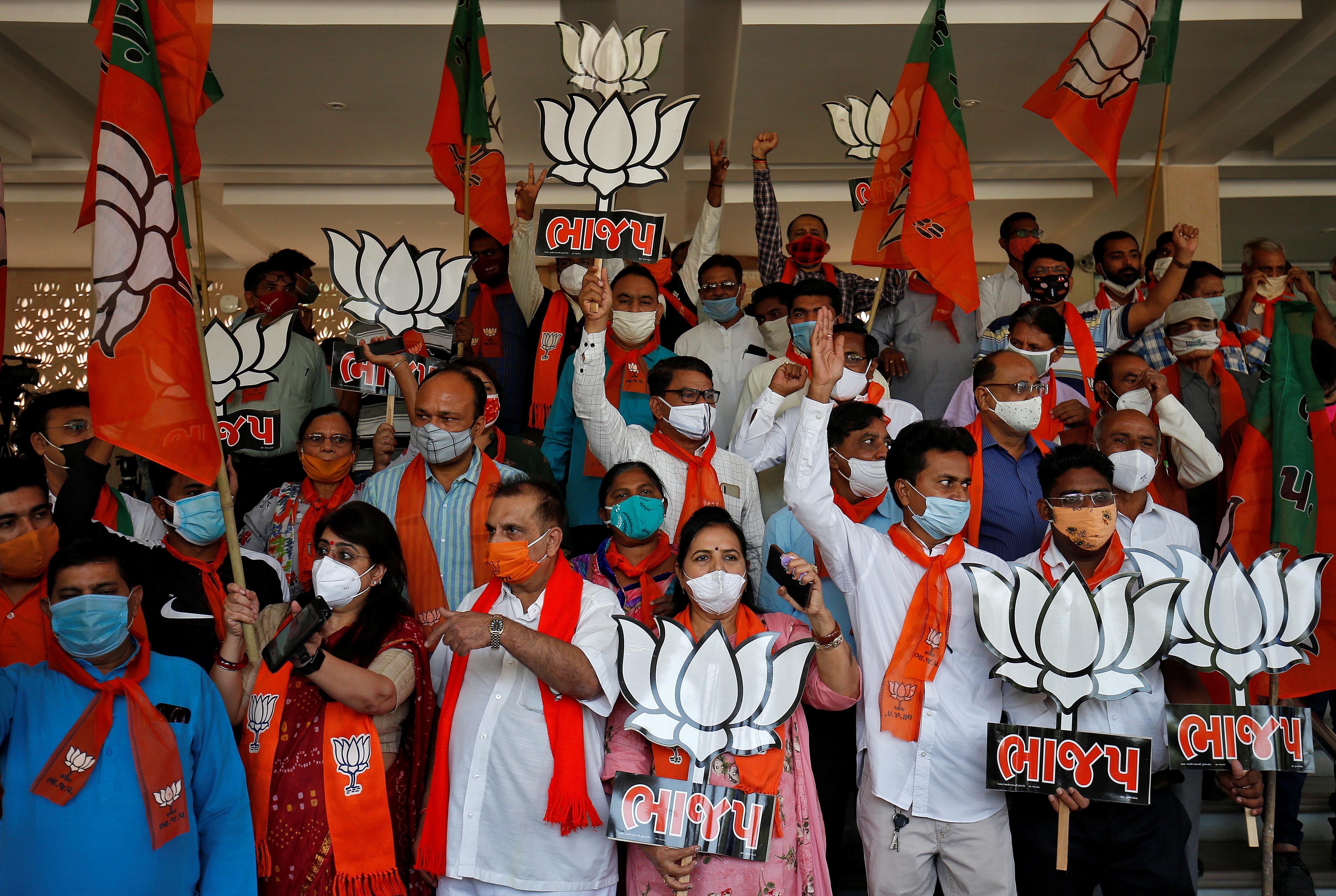Supporters of India's ruling Bharatiya Janata Party (BJP) hold their party symbols and flags as they gather to celebrate after learning of the initial poll results of the Bihar state assembly election and by-elections in Gujarat, Karnataka and Madhya Pradesh states, in Gandhinagar, India, November 10, 2020.  Photo: Reuters