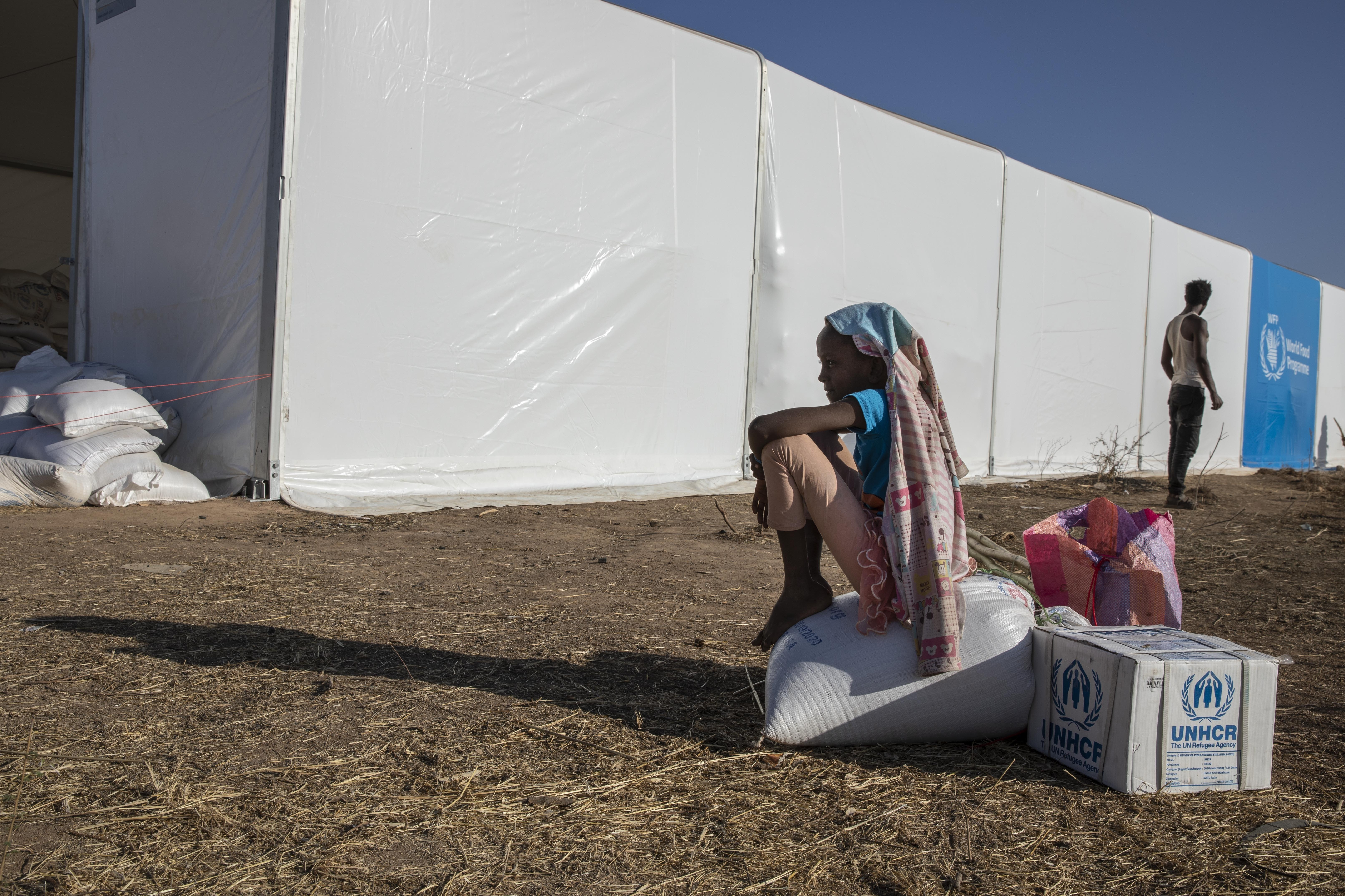 A Tigray refugee girl who fled the conflict in Ethiopia's Tigray region, sits on aid she received from the UNHCR and WFP at Umm Rakouba refugee camp in Qadarif, eastern Sudan, Tuesday, Nov. 24, 2020. Photo: AP