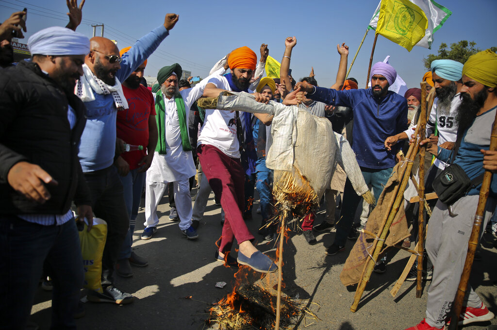 Protesting farmers burn an effigy of Indian Prime Minister Narendra Modi on a highway, refusing to move ahead unless they're allowed to proceed to their place of choice to protest, at the Delhi-Haryana state border, India, Saturday, November 28, 2020. Photo:AP