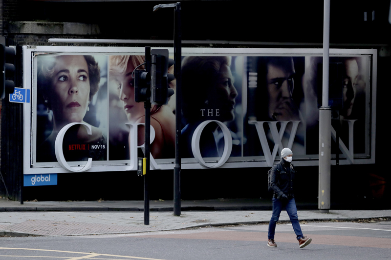 In this file photo dated Friday, Nov. 20, 2020, a man wearing a face mask walks past a billboard advertising 'The Crown' television series about Britain's Queen Elizabeth II and the royal family, during England's second coronavirus lockdown, in London. Photo: AP/File