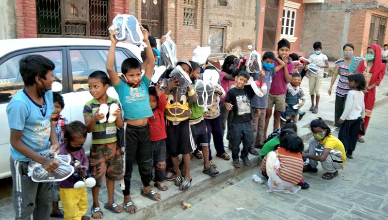 This undated image shows children holding shoes, slippers among other items provided by Shanti Sewa Griha, in Pashupatinath area, in Kathmandu. Photo: Prakash Singh/THT